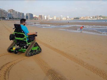 chico en silla ontrack paseando por la playa